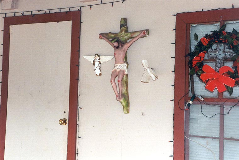 choctaw apache home displays a crucifix on the front porch photo