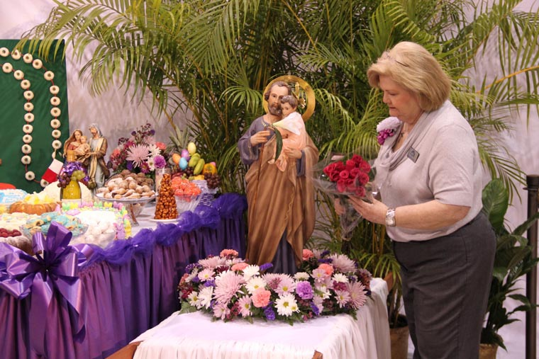St josephs altars faith in tradition decorating the altar carolyn musso places red roses near a statue of st joseph with baby jesus at the 2014 grandsons of italy altar photo maida owens sciox Images